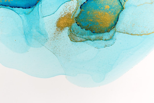 Alcohol ink blue and gold abstract stains on white background. drops watercolor transparent texture.
