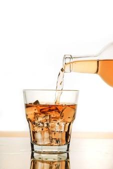 ボトルから氷を入れたグラスにアルコールを注ぎます。