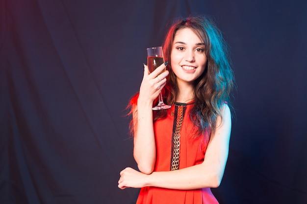 アルコール、人々、パーティーのコンセプト-赤いドレスを着た若いお祝いの女性。美しいモデルは、コピースペースで暗い背景にワイングラスを保持します