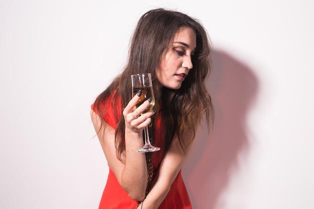 アルコール、人々、パーティーのコンセプト-赤いドレスを着た若いお祝いの女性。美しいモデルはワイングラスを保持します。