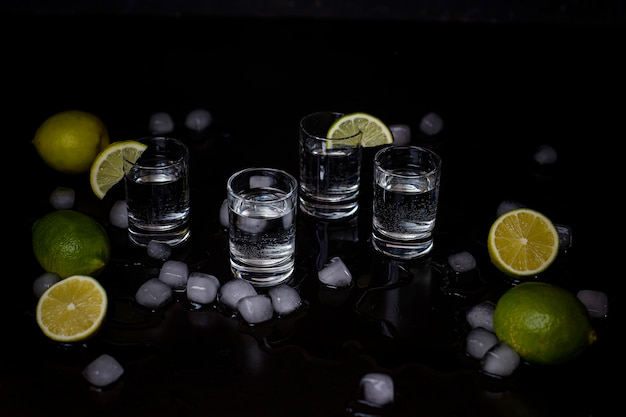 Alcohol shots with lime and ice cubes on black