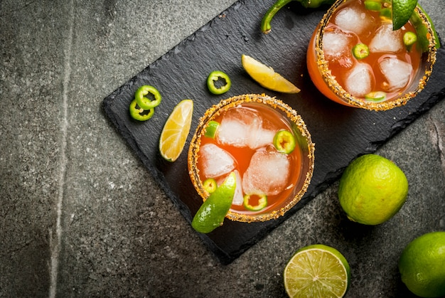 Alcohol. traditional mexican south american cocktail. spicy michelada with hot jalapeno peppers and lime. on a dark stone table. copyspace top view