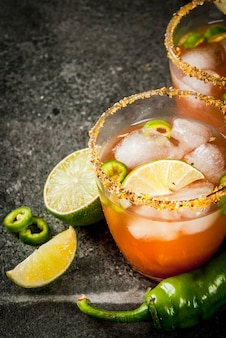 Alcohol. traditional mexican south american cocktail. spicy michelada with hot jalapeno peppers and lime. on a dark stone table. copyspace