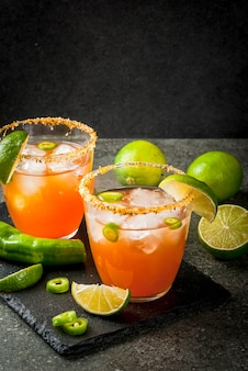 Alcohol. traditional mexican south american cocktail. spicy michelada with hot jalapeno peppers and lime. on a dark stone table.