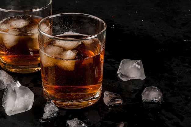 Alcohol whiskey cocktail with cola and ice