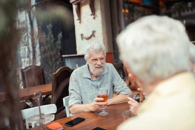 친구들과 술. 밖에 앉아 있는 동안 친구와 함께 술을 마시는 수염된 회색 머리 남자