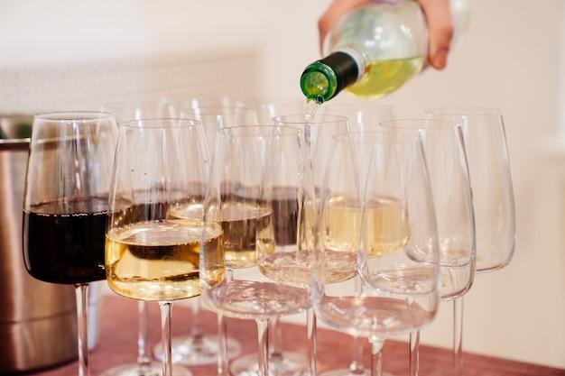 휴일에는 알코올 및 무 알코올 음료. 화이트 와인과 레드 와인을 와인 잔에 붓습니다.