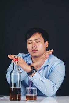 Алкоголик азиатский мужчина пьет виски с большим количеством бутылок