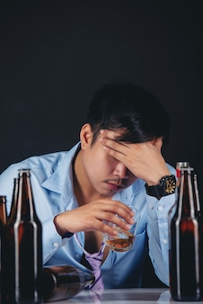 Alcoholic asian man drinking whisky with a lot of bottles