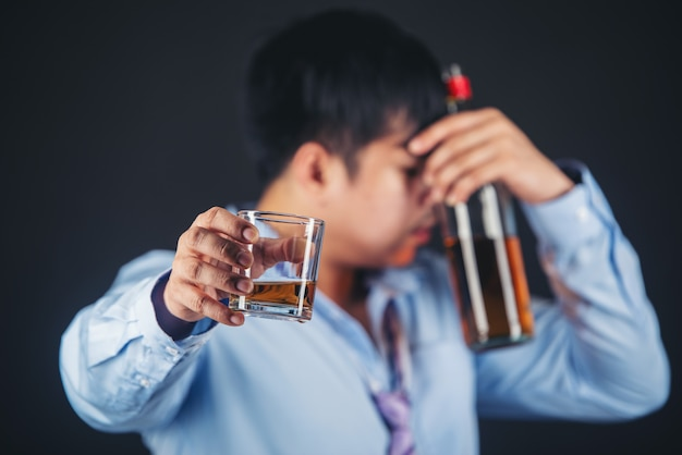Alcoholic asian man drinking whisky