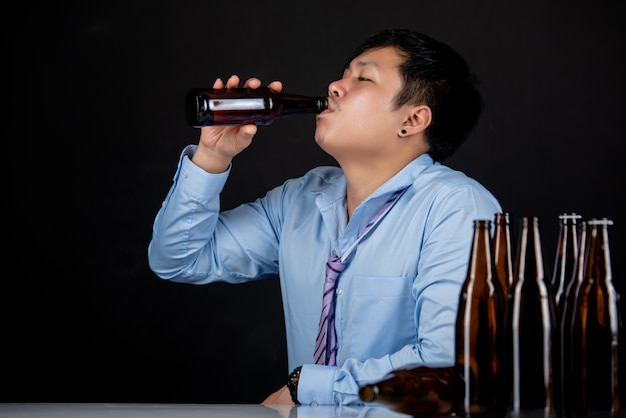 Alcoholic asian man with a lot of beer bottles