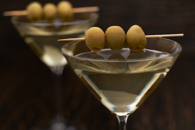Alcoholic beverage in glasses, close up. classic dry alcoholic beverage with green olives.