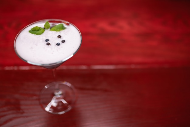 Alcoholic cocktail decorated with mint on a red wooden table. night club, close-up
