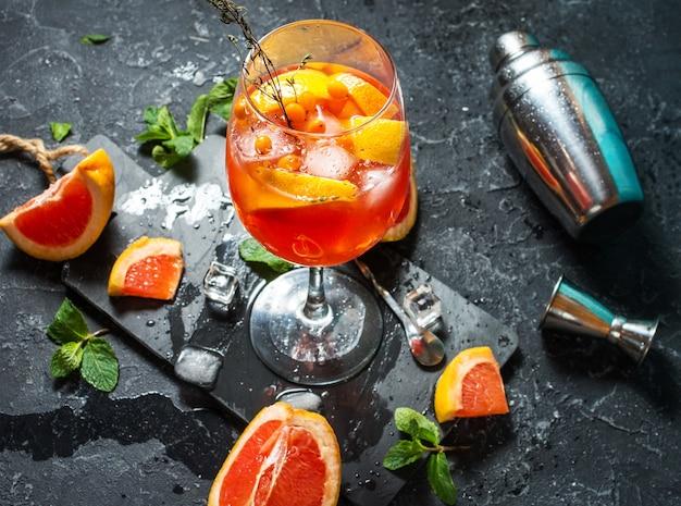 Алкогольный коктейль на каменной доске с грейпфрутом и льдом