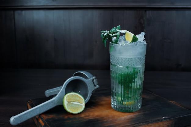 레몬이나 라임에서 주스를 얻을 수있는 전문 도구 옆에는 얼음과 신선한 민트 잎과 라임 조각이 들어간 알콜 칵테일