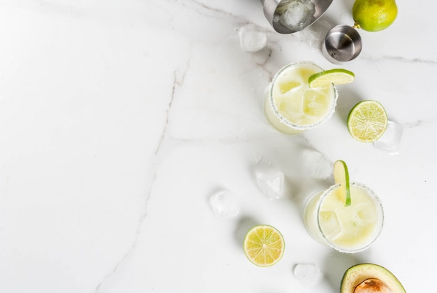 Alcoholic cocktail recipes and ideas. avocado and lime margarita with salt, on a white marble kitchen table. copyspace top view