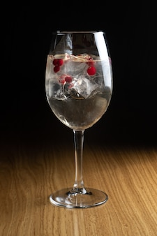 Алкогольный коктейль spritz с клюквой и льдом в высоком прозрачном фужере на деревянном столе