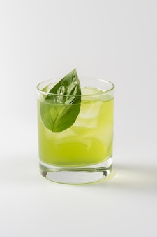 Alcoholic cocktail with basil in glass goblet