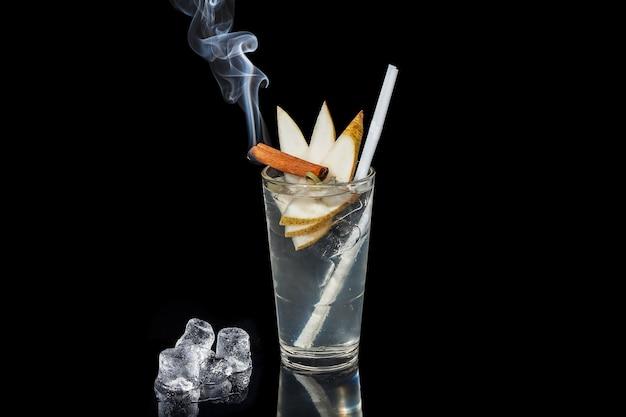 Алкогольный коктейль с палочкой корицы и грушей на черном фоне