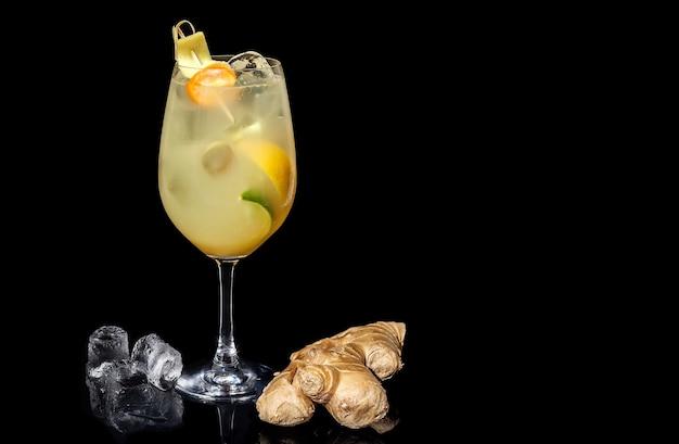 Алкогольный коктейль с имбирем, лаймом и апельсином на черном фоне
