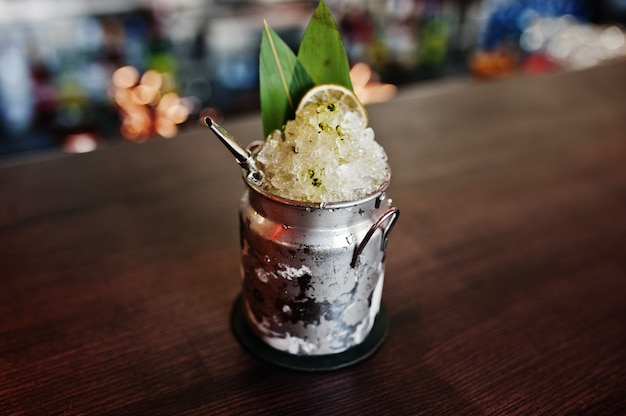 Alcoholic cocktail with ice in can glass on bar table