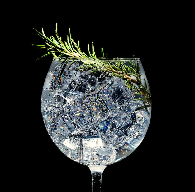 Alcoholic cocktail with ice. soda and rosemary on a black space