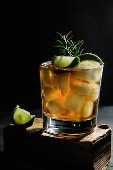 어두운 배경 어두운에 유리에 라임과 로즈마리와 얼음 위스키 칵테일 알콜 칵테일 photo