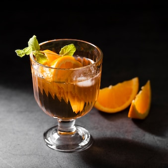 Alcoholic cocktail with oranges close up
