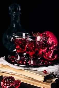 金属製のトレイにザクロの果実とアルコールカクテル