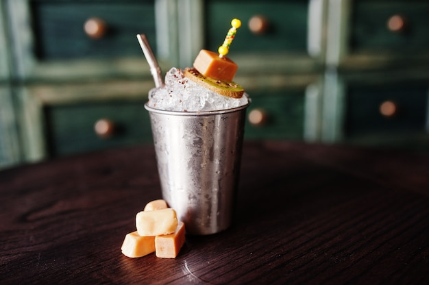 Alcoholic cocktail with sweets and candies in small silver bucket at bar table
