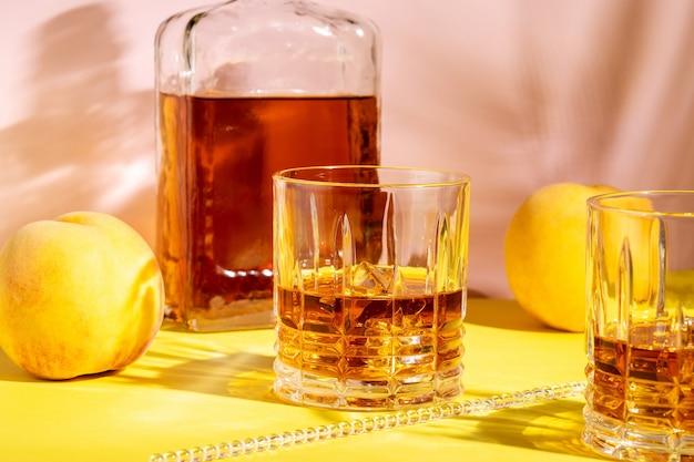 明るい背景に桃とグラスでアルコール飲料。