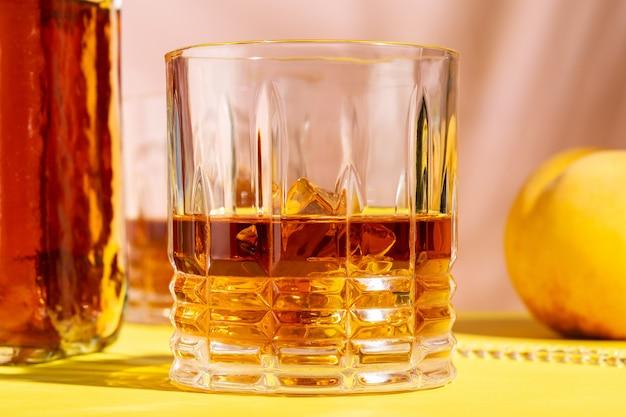 Алкогольный напиток в стакане с персиком на ярком фоне.