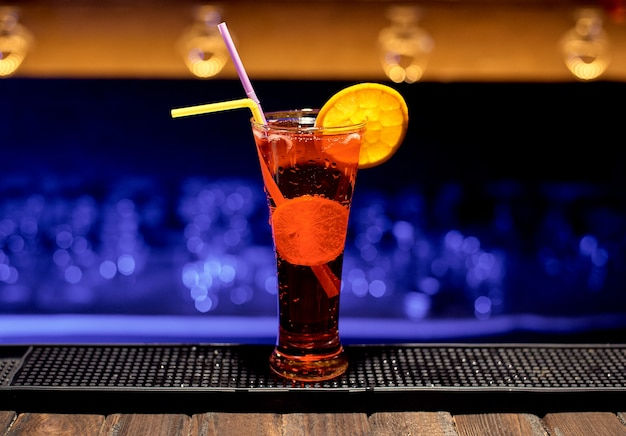 Alcoholic drink on a jay of a bar in a nightclub of red color.