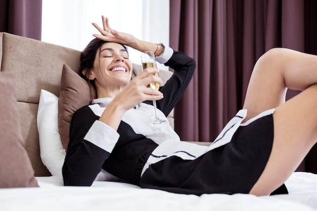アルコール飲料。ホテルのベッドに横たわっている間シャンパンでグラスを保持しているうれしそうな笑顔の女性