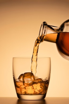 Алкогольный напиток, разлитый из стакана из бутылки на оранжевом золотом фоне. виски, коньяк или бурбонский виски.