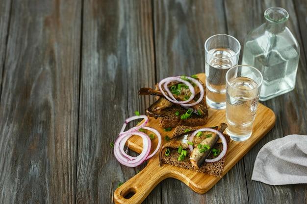 木製の壁に魚とパンのトーストとアルコール飲料。アルコールの純粋なクラフトドリンクと伝統的なスナック。ネガティブスペース。食べ物を祝っておいしい。上面図。