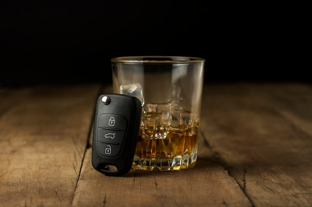 Alcoholic drink with ice in a glass and car keys on a wooden background. drunk driving concept, stop drinking and driving.
