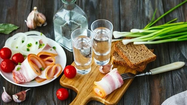 나무 벽에 라드와 녹색 양파와 알콜 음료. 알코올 순수 공예 음료와 전통 간식, 토마토 및 빵 토스트. 부정적인 공간. 음식과 맛있는 것을 축하합니다.