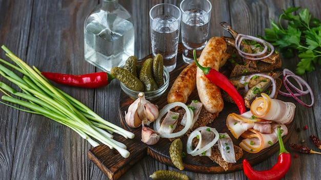 Alcoholic drink with lard, salted fish and vegetables, sausages on wooden wall. alcohol pure craft drink and traditional snack, tomatos, onion, cucumbers. negative space. celebrating food and delicious.