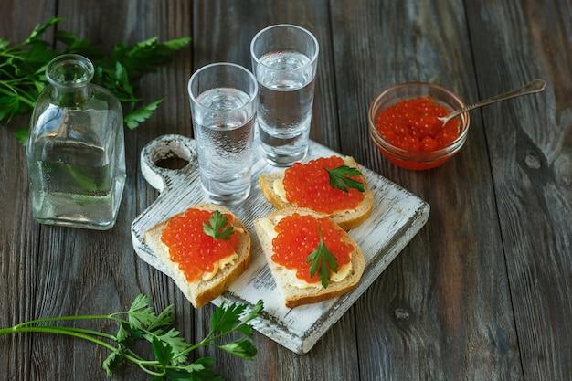 木製の壁にサーモンキャビアとパンのトーストとアルコール飲料。アルコールの純粋なクラフトドリンクと伝統的なスナック。ネガティブスペース。食べ物を祝っておいしい。上面図。