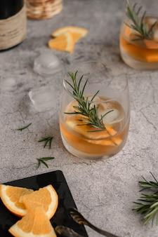 スライスしたオレンジと蒸しローズマリーのアルコール飲料