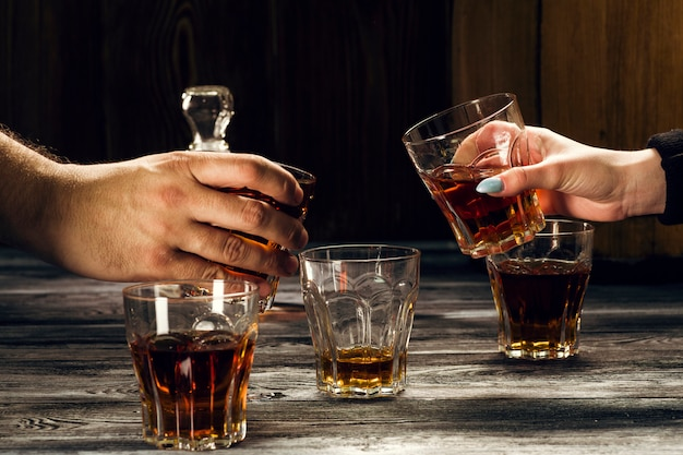 Alcoholic drinks in the hands of a man and a woman over a table with full glasses