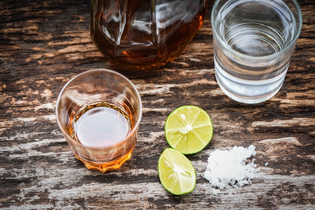 Alcoholic drinks and lemon salt on rustic wood background brandy in a glass with alcohol bottles and water, vodka rum cognac tequila and whiskey