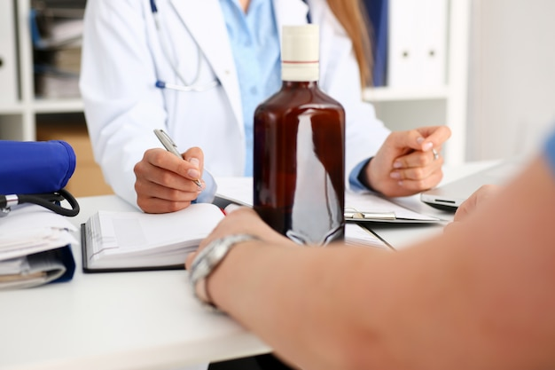 Alcoholic hold in arm empty bottle at doctor reception