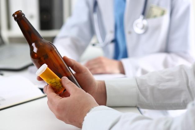 アルコール依存症は、医師の受付事務所のクローズアップで空のボトルを手に持っています。