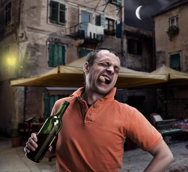 Алкоголик открывает бутылку вина на улице
