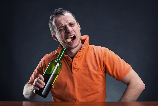 Алкоголик открывает бутылку вина