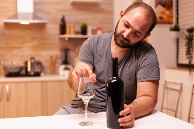 Alcoholic man being depressed and frustrated holding bottle of red wine in kitchen. unhappy person disease and anxiety feeling exhausted with having alcoholism problems.