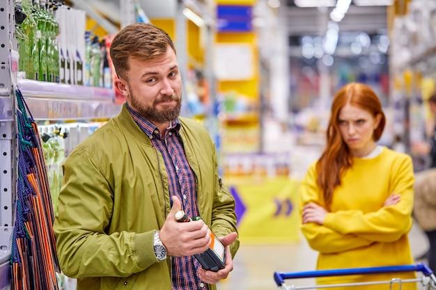 彼女の気分を害したガールフレンドが立っている間、アルコール依存症の男性はスーパーマーケットでアルコールボトルを手に立っています、彼女は彼の中毒に不満を持っています