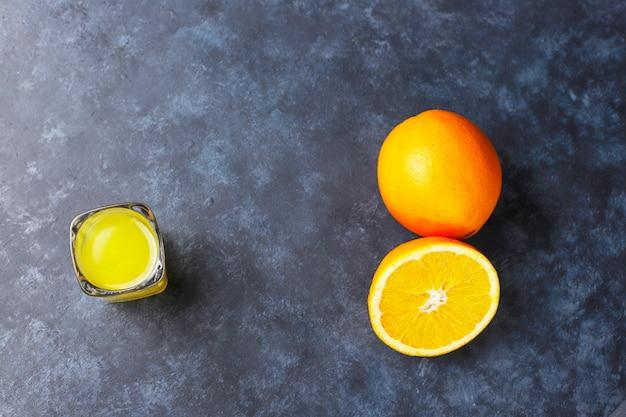 Alcoholic orange drink in shot glass with orange slice and orange on dark background